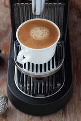 Cup of freshly brewed espresso from a capsule.