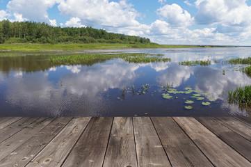 Деревянный пол террасы на фоне озера с кувшинками
