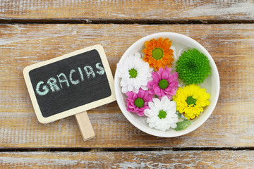 Gracias (thank you in Spanish) on blackboard and Santini flowers