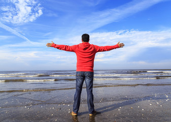Man with his hands up on the beach
