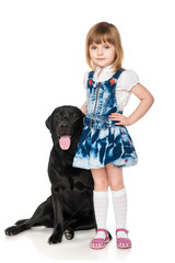 Beautiful little girl hugging with a black Labrador