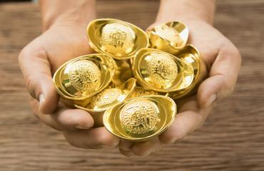 Hand hold chinese gold ingots