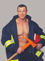 Portrait of fireman posing on grey background