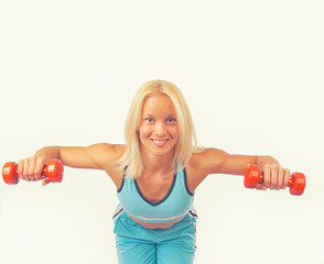 Good-shaped athletic girl poses and holds dumbbells
