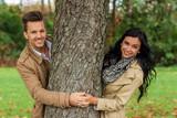Fototapety Verliebtes Paar hinter einem Baum