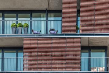 Three topiary trees on an apartment balcony
