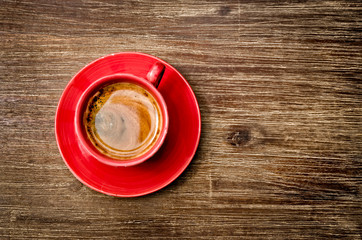View of coffee in red cup on wooden vintage table