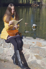 Beautiful girl-student sits on parapet near the city pond in sun