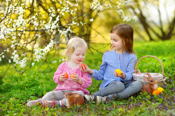 Two little girls playing in a garden on Easter