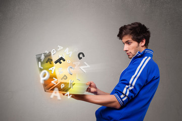 Attractive young man hoding notebook with colorful letters