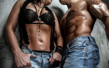 Muscular male and female in blue jeans on grey background.