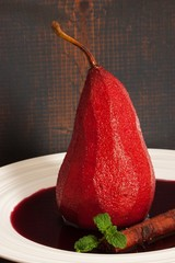 Poached pear on wooden background