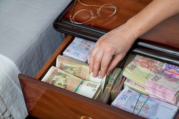 Hand pulls out banknote from the bedside table