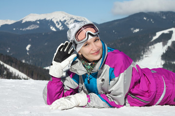 Beautiful young girl in ski suit lying in the snow