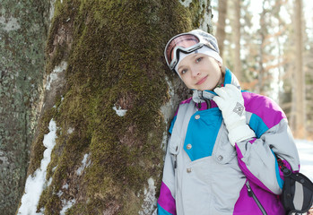 Skier woman standing near the trunk of a tree in winter forest