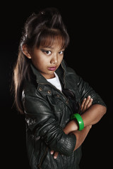 Tanned girl rocker in leather jacket with a crest on the head