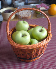 Green apples in brown wicker basket on kitchen desk