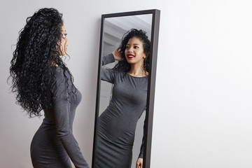 pretty happy woman watching on herself in a big mirror