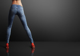 perfect shaped woman wearing skinny jeans in a dark room - 77835304