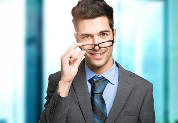 Confident smiling young manager holding his glasses