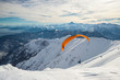 Paraglider launching from snowy slope - 77838345
