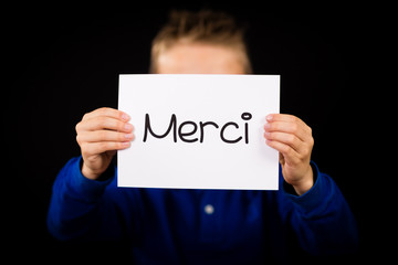 Child holding sign with French word Merci - Thank You