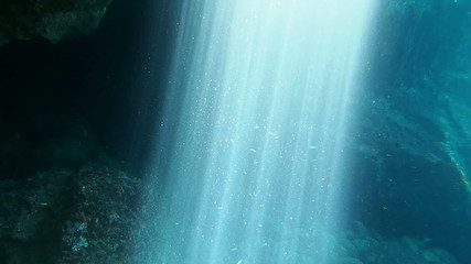 Sunbeams shining in an underwater cave