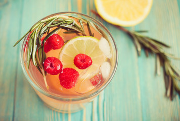 detox water in cup with raspberry, rosemary and citrus, close-up