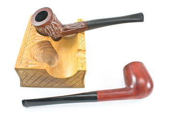 Two tobacco pipes on wooden holder isolated on white