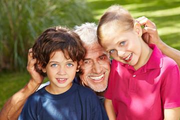 Großvater mit Enkeln im Garten
