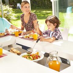 Kind nimmt Salat mit Kelle am Tisch