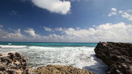 Ocean with waves and rocks on caribbean beach, Cancun, Mexico