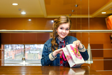 Beautiful girl in a cafe opens a gift bag and smiling