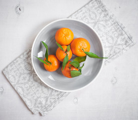 Tangerines on white wooden background. Grey napkin