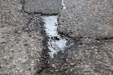 The pit on the asphalt road with puddle