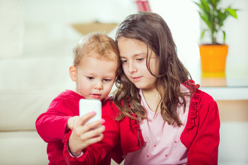 Happy brother and sister take pictures with telephone