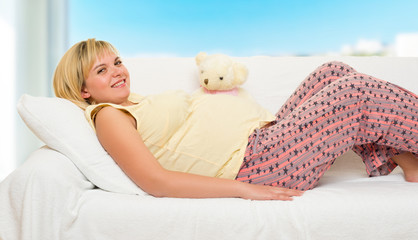 Pregnant woman in bed with red hearts