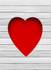 red heart hole in white wooden background