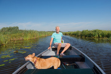 Senior man with dog in motor boat