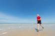 canvas print picture - Elder man running at the beach