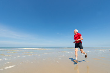 Elder man running at the beach