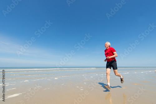 canvas print picture Elder man running at the beach