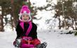 Little girl sledging in the snow