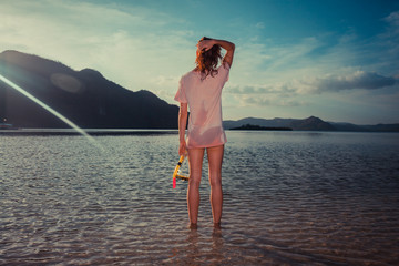 Woman standing on tropical beach with snorkel