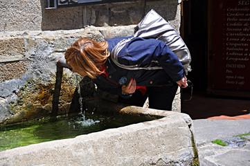 Mujer bebiendo agua de una fuente pública