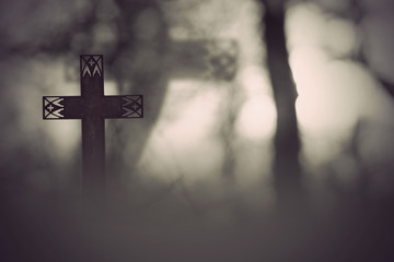 rusty metal cross in spooky dark landscape