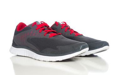 A pair of gray running shoes with red shoelaces on a white backg