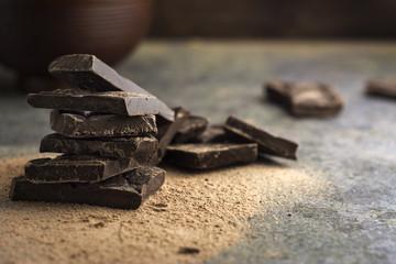 pieces of dark chocolate stacked on grunge background