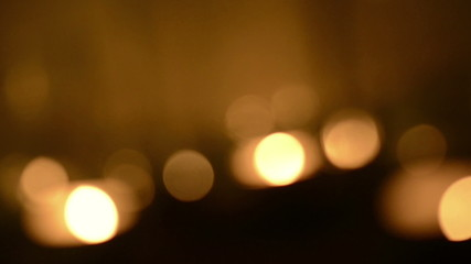 Rotating background blur of candles burning with defocused bokeh