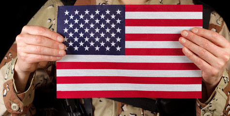 American flag being held by male soldier